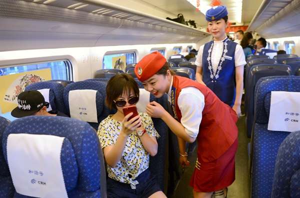An attendant serves a passenger on a high-speed train at Hohhot East Train Station in the Inner Mongolia autonomous region on Thursday morning.[Photo/China Daily]