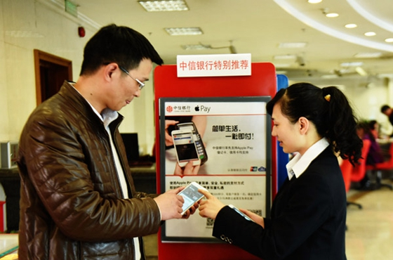 A man learns how to use Apple Pay at a bank in Hangzhou, capital of Zhejiang province. [Photo/China Daily]