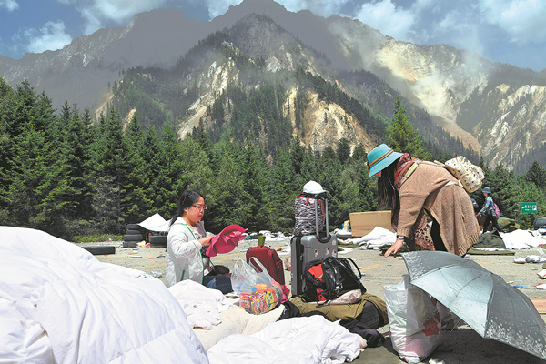 Tourists gather their belongings at a hotel parking lot as they prepare to leave the mountainous earthquake zone on Wednesday, August 9, 2017. [File Photo: Xinhua]