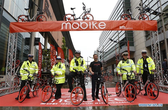 Manchester Metropolitan Police pose for a group photo during the launch of Mobike in Manchester, Britain on June 29, 2017. [Photo/Xinhua]
