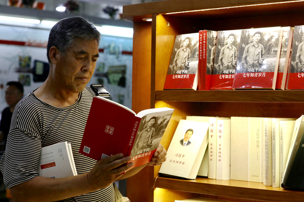 A customer reads Xi Jinping's Seven Years as an Educated Youth in Wangfujing Bookstore in Beijing on Sunday. [Photo by Zhu Xingxin/China Daily]