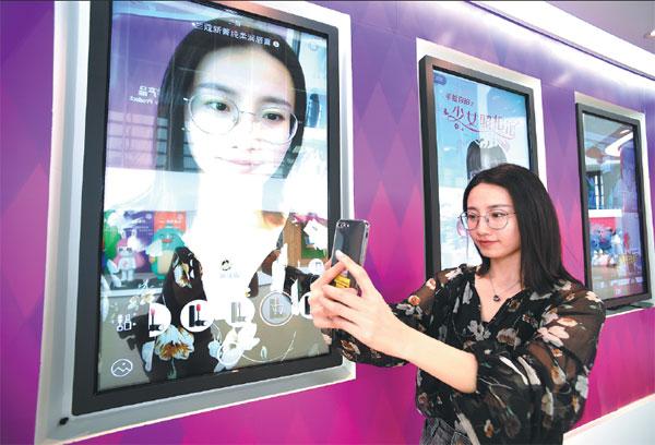 An employee of Meitu Co, Xiamen's largest high-tech enterprise, demonstrates a new mobile phone app that prettifies photos. Jiang Kehong / Xinhua