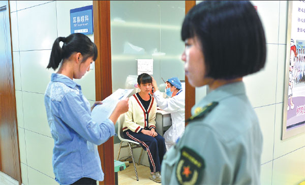 Teenagers have their ears checked during the extensive physical examination process for military recruits in Kunming, Yunnan province, on Monday. Candidates must pass every item on the checklist to be accepted. Gao Wei / For China Daily