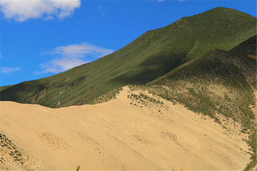 The photo shows five Chinese characters which literally means 'Green Chinese Dream' on the mountains close to the sand control area under the sand control project of Shannan in China's Tibet Autonomous Region.