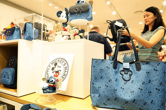 Visitors examine products at a Disney shop in Shanghai, which opened last week. [Photo/China News Service]