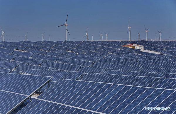 A photovoltaic power plant and a nearby wind power farm in Zhangjiakou, north China's Hebei Province, Jan. 19, 2015. The local government has combined air pollution control and energy structure change by using photovoltaic and wind power in recent years. [File photo/Xinhua]