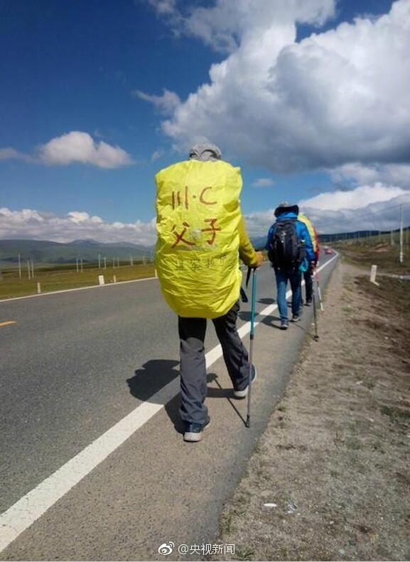 Zhang Wei and his 12-year-old son walk along the Sichuan-Tibet highway during their 1,700-kilometer-long journey from Zigong City in Sichuan Province to Lhasa City in Tibet Autonomous Region. [Photo from Weibo.com]