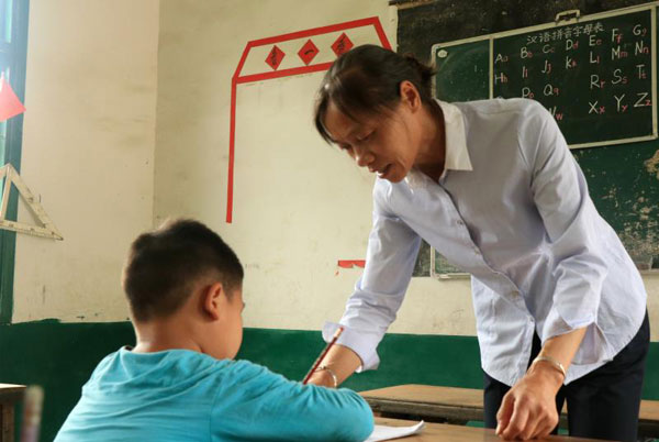 Yu Xiaoli helps a student with his studies in a class in Zongshujiao village in Central China's Hunan province.[Photo by Hu Jiangyong / chindaily.com.cn]
