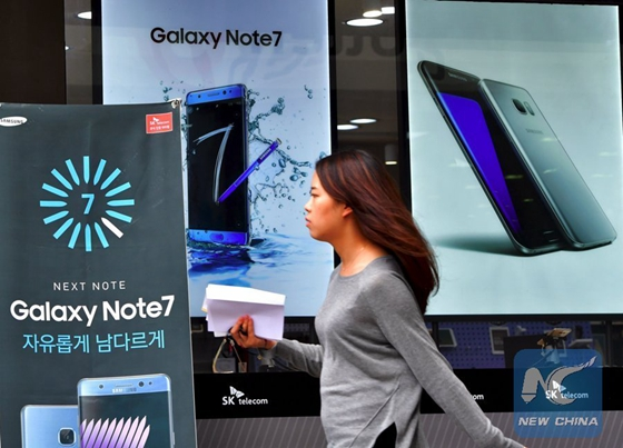 A woman walks past billboards of Samsung Galaxy Note 7 (L) and Galaxy S7 (R) at a mobile phone shop in Seoul on September 12, 2016. [Photo/Xinhua]
