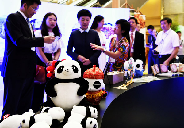 UN World Tourism Organization assembly attendees look over promotional products in Chengdu, Sichuan province, on Wednesday. [Photo/China News Service]
