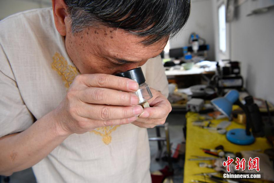 n Longquan, a master of microscopic carving, scrutinizes his works at his studio in Kunming, southwestern China's Yunnan province, Sept 12, 2017. [Photo/Chinanews.com]