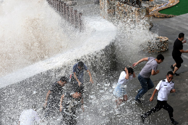 A wave crashes into a barrier in Wenling, Zhejiang province, on Thursday ahead of Typhoon Talim. [Photo/China Daily]