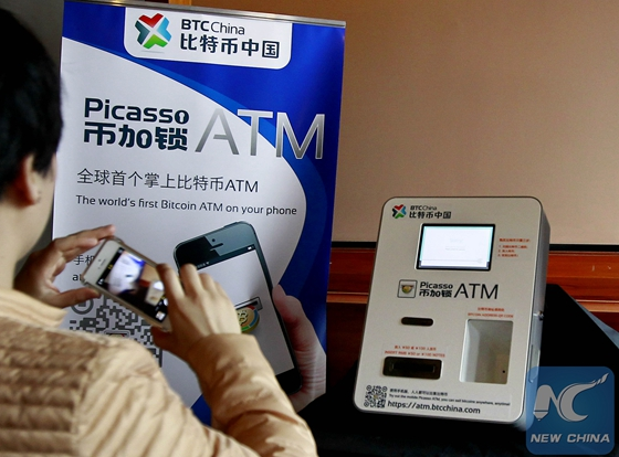 A citizen takes photos of a bitcoin ATM in east China's Shanghai, April 16, 2014. [Photo/Xinhua]