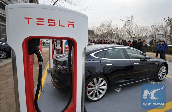 Owners have their Tesla electric cars recharged at a Supercharger station in north China's Tianjin, Jan. 24, 2015. [Photo/Xinhua]
