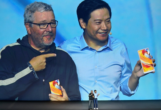 Lei Jun (right), chief executive officer of tech company Xiaomi, presents a full-screen smartphone with its French designer, Philippe Starck, at a new product launch event in Beijing on Sept 11. [Photo/China Daily]