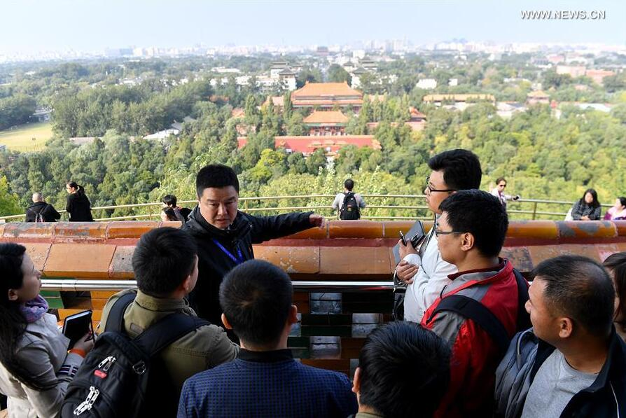 Song Kai (L, 2nd Row), Deputy Director of Jingshan Park, introduces the Central Axis of Beijing to journalists in Beijing, capital of China, Oct. 12, 2017. The Press Center of the 19th National Congress of the Communist Party of China (CPC) organized a reporting tour along the Central Axis of Beijing on Thursday. Chinese and foreign reporters visited scenic attractions such as the Jingshan Park, Yongding Gate and the Olympic Tower. (Xinhua/Li Xin)