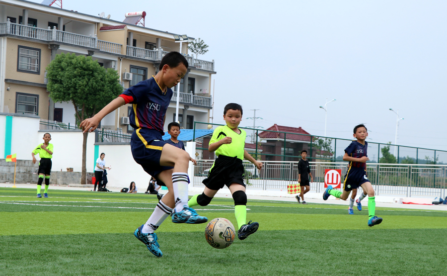 Primary school students from Qianshan county, Anhui province, compete in a soccer game on Oct 1. [Photo / China Daily]