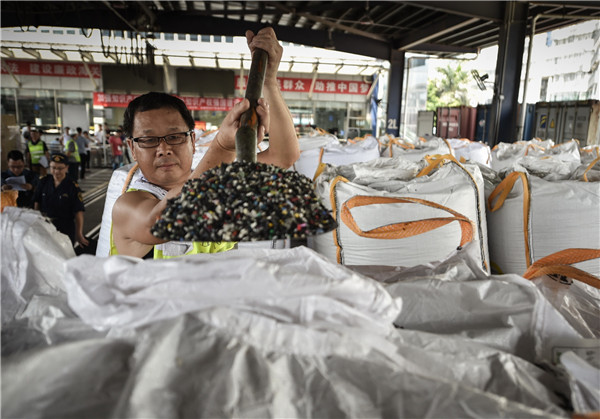 A worker for Shenzhen Customs in Guangdong province shows the plastic waste that was seized in June last year.[Photo by Mao Siqian/Xinhua]