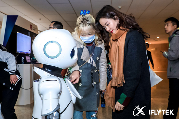 People interact with a robot developed by iFlytek on Nov. 9, 2017. [Photo provided to China.org.cn]