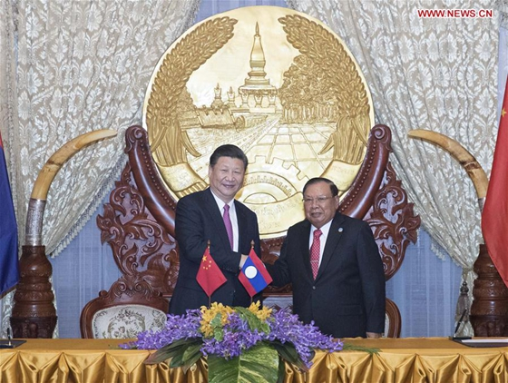 Chinese President Xi Jinping (L), also general secretary of the Communist Party of China Central Committee, shakes hands with Bounnhang Vorachit, general secretary of the Lao People's Revolutionary Party (LPRP) Central Committee and president of Laos, while jointly witnessing the signing of bilateral cooperation documents after their talks in Vientiane, Laos, Nov. 13, 2017. [Photo/Xinhua]