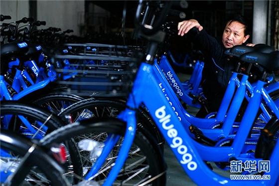 A staff member examines the newly manufactured bluegogo bikes. [Photo/Xinhua]