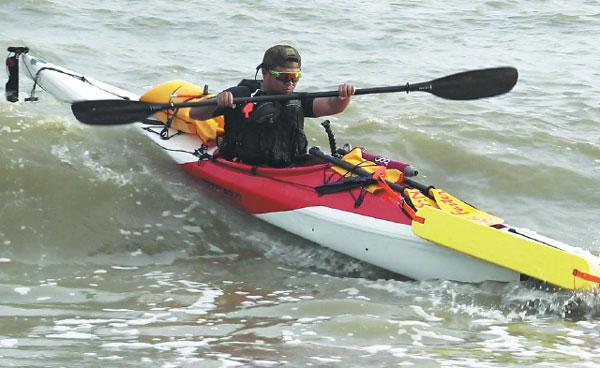 Zhen Shilun paddles his kayak along part of China's 18,000 kilometers of coastline. [Photo/China Daily]