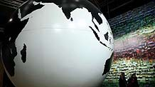 Two women are seen beside a globe model at the empty hall of the Bella Center during the United Nations Climate Change Conference in Copenhagen, capital of Denmark, December 19, 2009.