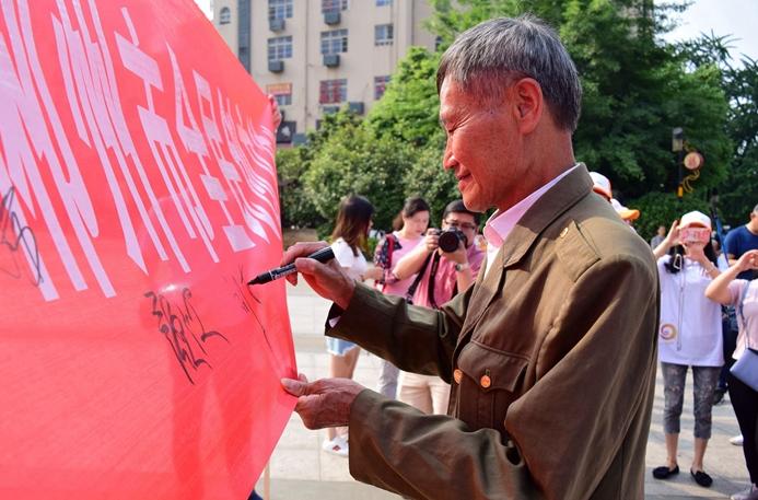 郴州志愿者携手道德模范刘真茂开展公益活动促创文