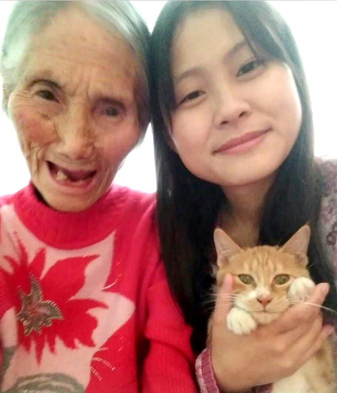 Liu Lin taks a photo with her gramdma and their pet cat at their rented home. (Photo: VCG)