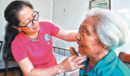 A nurse at Sijiqing Nursing Home combs the hair of an elder resident at the Beijing facility. President Xi Jinping visited there in December 2013 and residents said they were energized by his presence. [Photo/Xinhua]