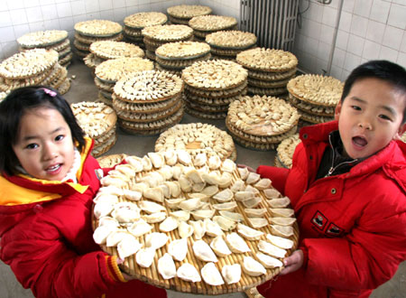two children carry dumplings at a communal dinner to celebrate the lunar new year at a village in daxing district of beijing february 6 2008 the lunar new - How Long Is Chinese New Year