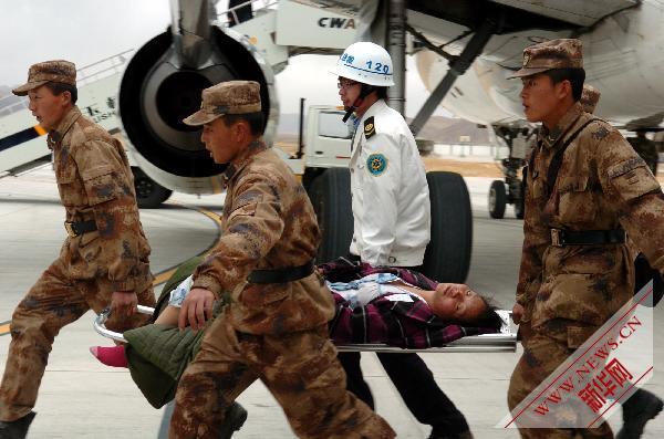 地震危重伤员被解放军战士和机场急救人员抬往救灾飞机.-抢救伤员
