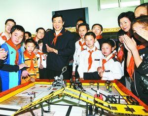 ... 教室,薄熙来兴致勃勃地观看孩子们制作的机器人