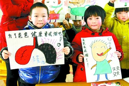 内乡县幼儿园的小朋友们在展示他们送给爸爸的新年礼物――戒烟宣传画