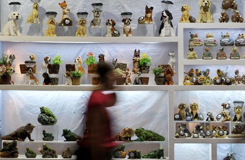 4月23日,一位客商经过第109届广交会第二期的一个工艺品展位.