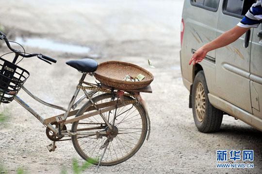 """旁,过往车辆往自行车后座的箩筐投掷""""过路费""""(6月24日摄).黄孝图片"""