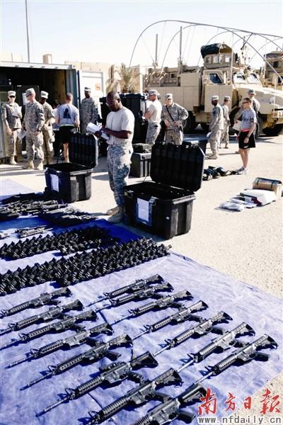 3日,美军士兵在伊拉克一处军事基地检查即将运走的武器. 新华社发