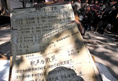 唱歌点,写着《祖国慈祥的母亲》、《歌声与微笑》等歌词的纸张方