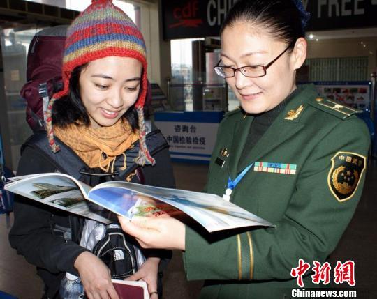 云南 高丽萍/边检警官高丽萍在向泰国游客介绍云南著名旅游景点。王保祥摄