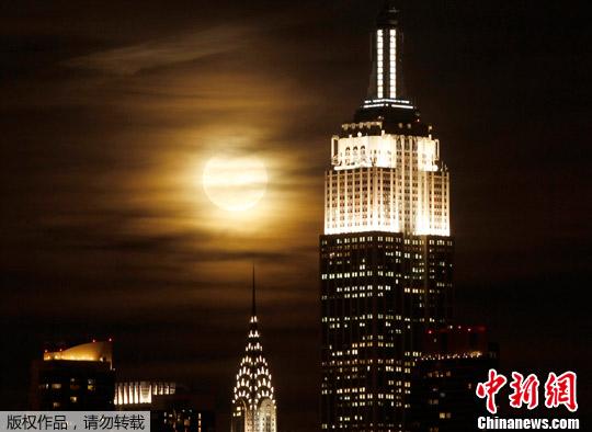 满月在曼哈顿的帝国大厦和克莱斯勒大厦旁升起.-纽约曼哈顿圆月当