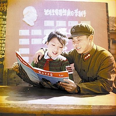 """1962年,雷锋和本溪路小学""""五好""""学生陈雅娟在阅读《解放军画报》"""