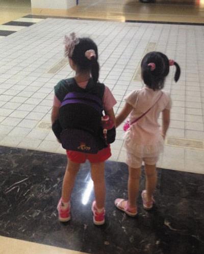 俩女儿背书包手拉手背影温馨