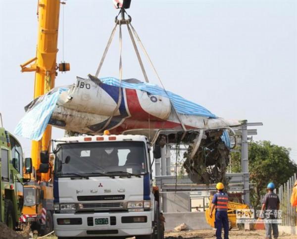 台军方人员将坠落的飞机机身残骸吊挂上拖车准备拖离
