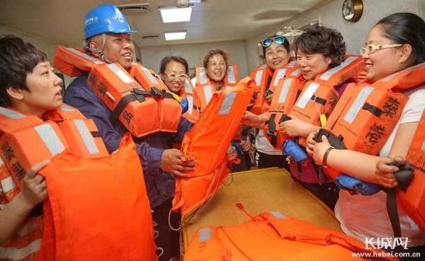 志愿者指导社区居民如何正确穿戴救生衣.