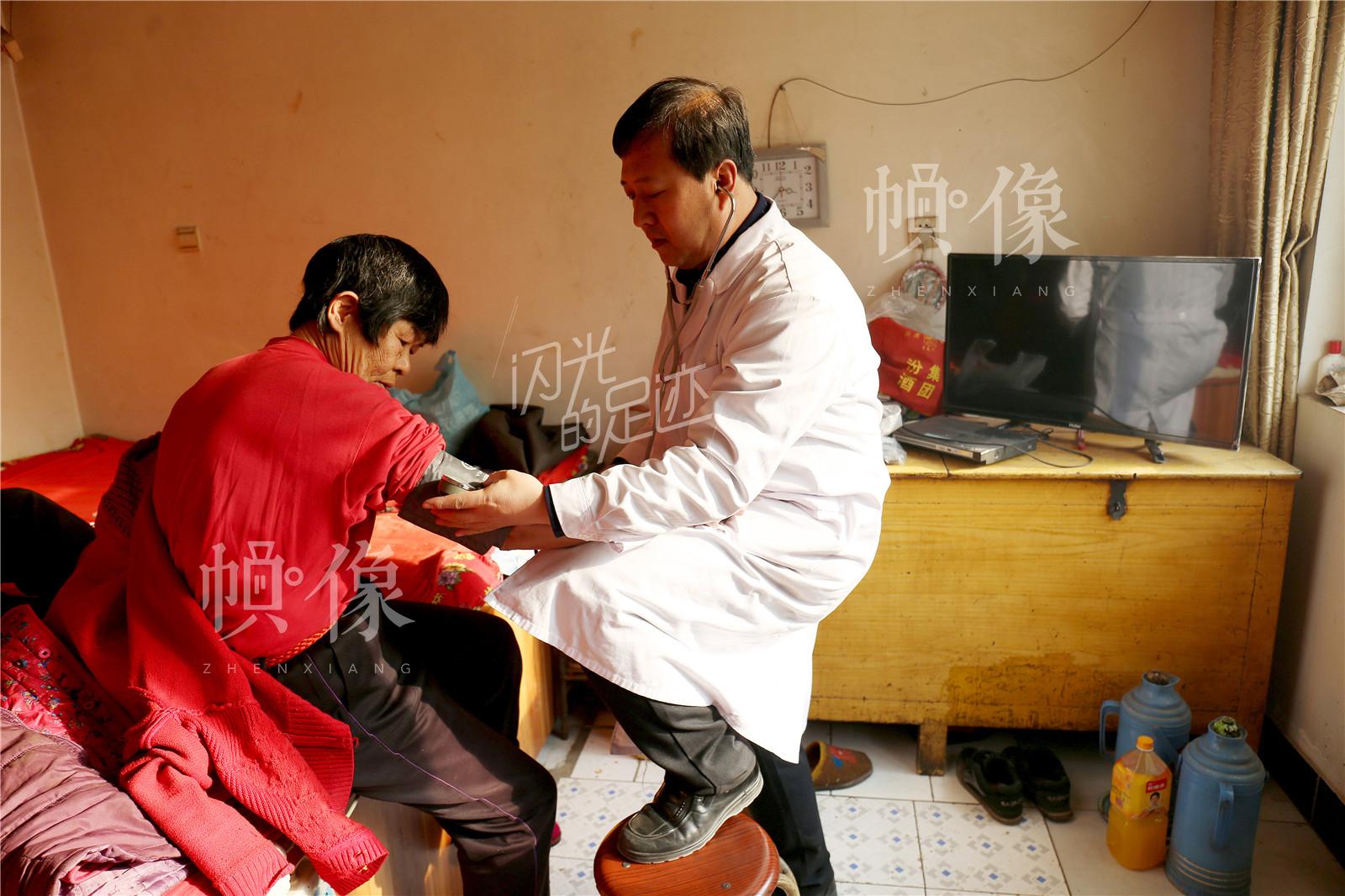 张坊镇东关上村周景荣今年65岁,患有甲状腺、动脉硬化、脑血管等疾病,王金海测量血压后准备回去给她开几副中药进行调理。中国网记者 黄富友 摄