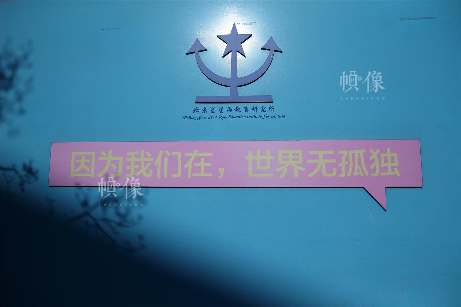 """2017年3月27日,北京星星雨教育研究所,操場的墻上有一句口號""""因為我們在,世界無孤獨""""。中國網記者陳維松 攝"""