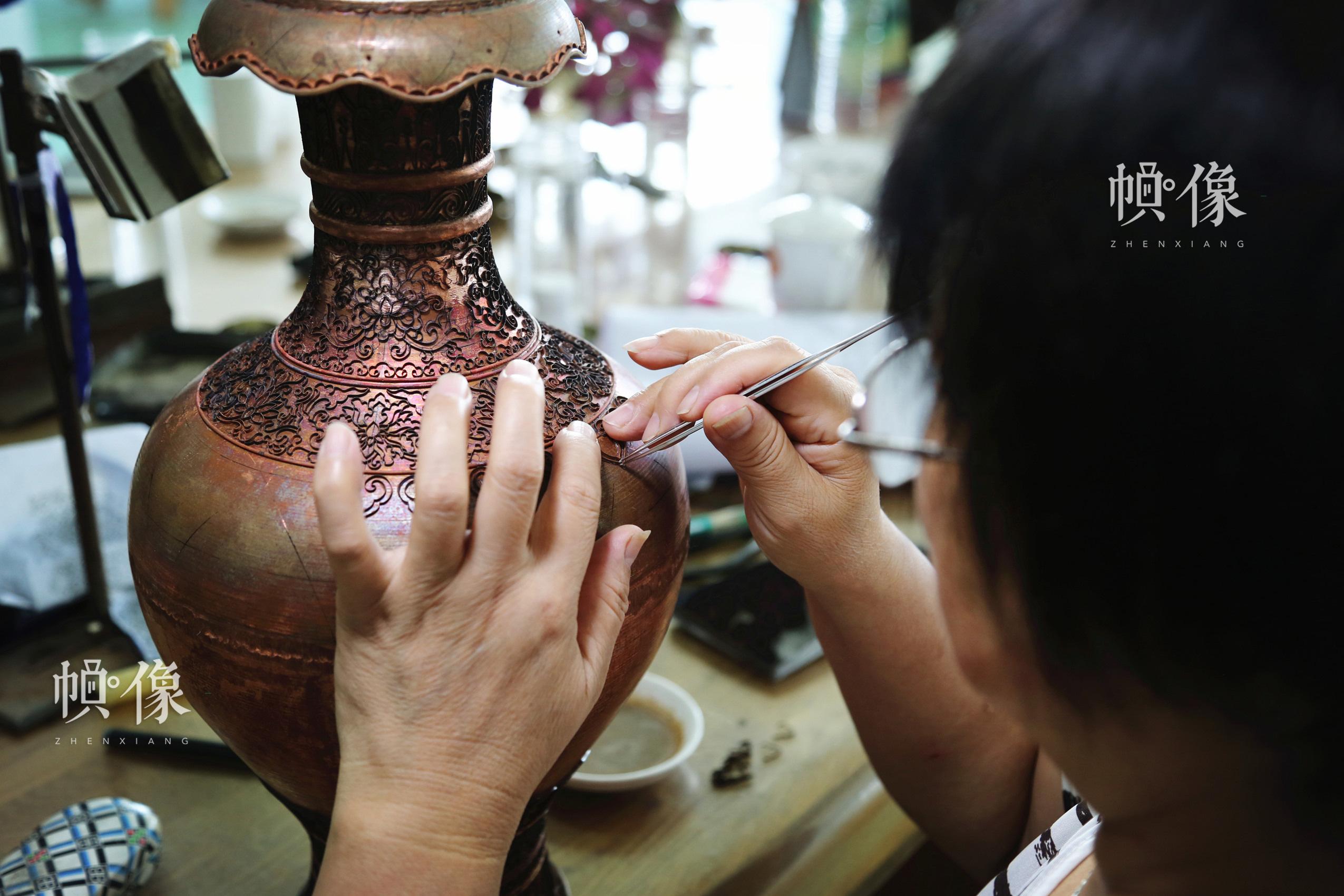 2017年9月5日,景泰藍工匠將製作好的銅絲貼在銅胚上。中國網記者 趙超 攝