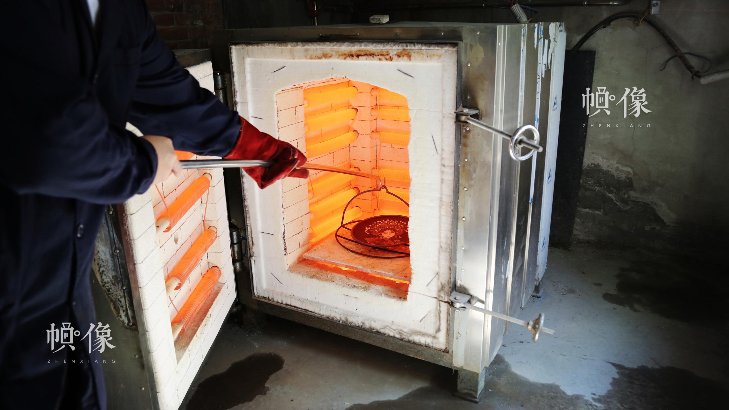 工匠把待烧的铜胚放到高温达800多度的电火炉中烧制。中国网记者 赵超 摄