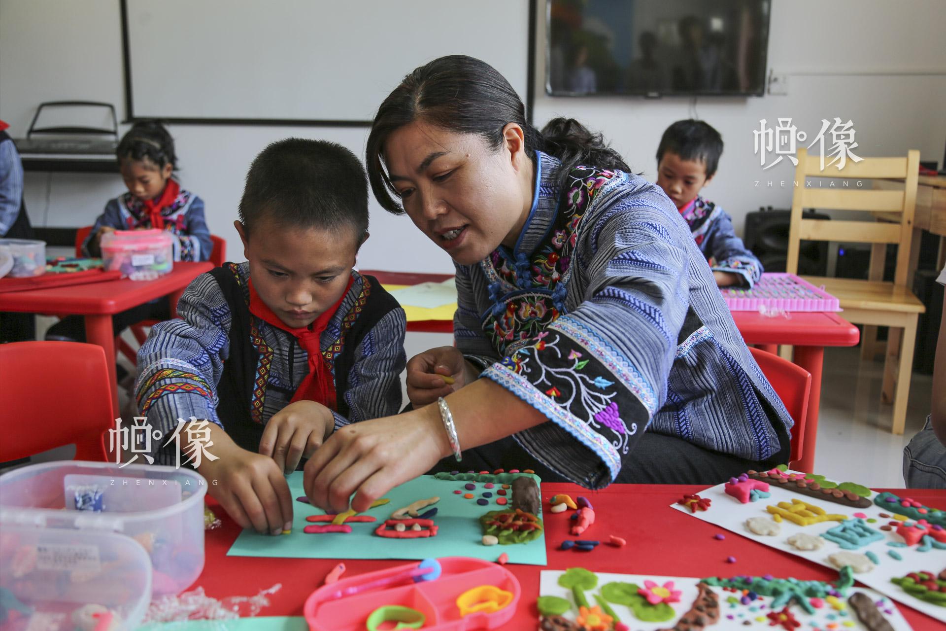 """余梅(右)是海庄村""""儿童快乐家园""""的一名志愿者,也是海庄小学三年级的班主任。罗天梁的爱心妈妈余梅说,""""孩子们说我以前只能在学校关心他们。现在有了'儿童快乐家园',我可以在课外教他们看书、做作业。我觉得这个家园给了孩子们一种家的感觉,一个快乐的天地。""""中国网记者 黄富友 摄"""