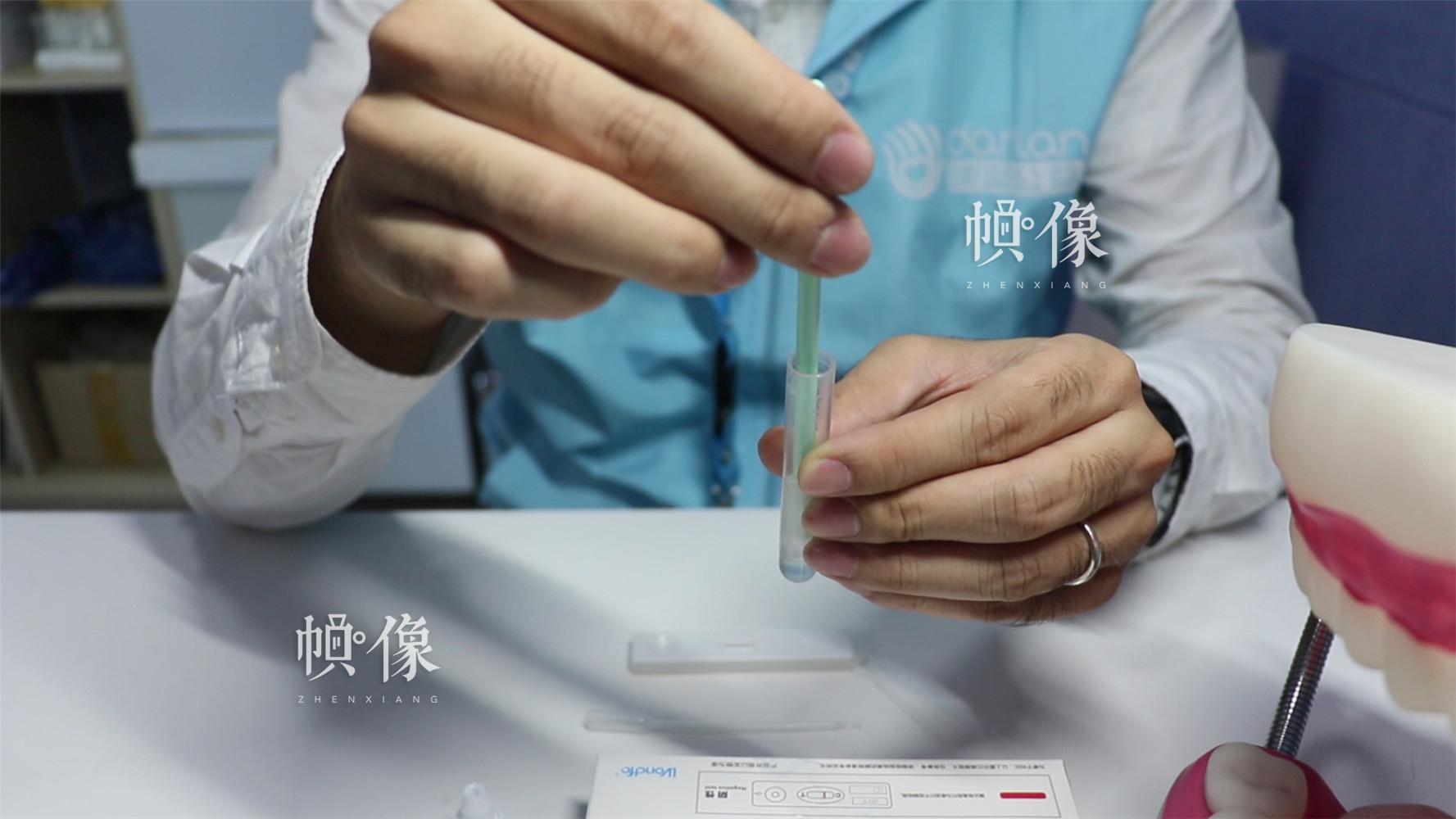 2017年11月22日,检测志愿者进行检测样本提取。中国网实习记者 朱珊杉 摄